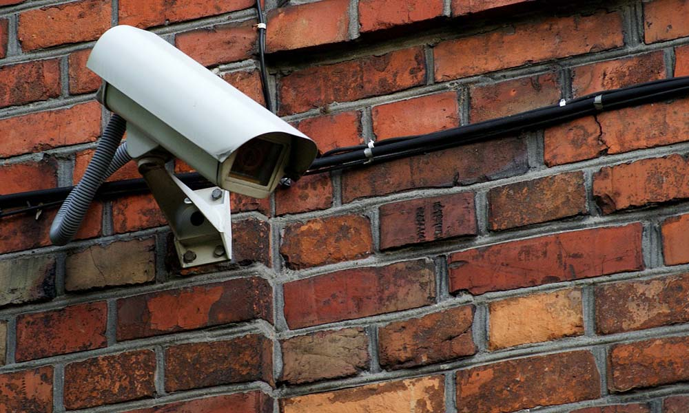 Protecting Your Business During Civil Unrest - Security Camera Mounted On A Brick Wall